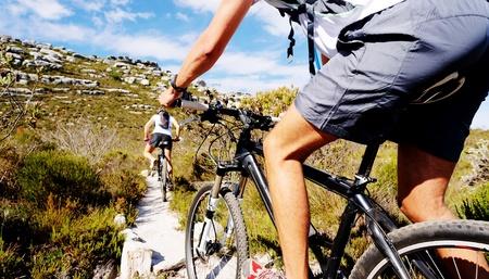 andando en bicicleta: Vista granangular de un ciclista en bicicleta en un sendero natural en las monta�as. dos personas que viven un estilo de vida saludable Foto de archivo