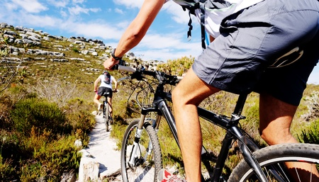 biking: Wide angle view of a cyclist riding a bike on a nature trail in the mountains. two people living a healthy lifestyle