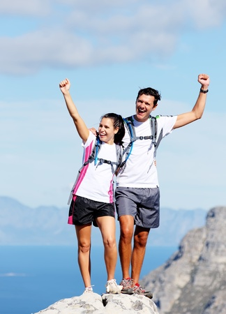 Hiking couple happy to reach the top of a mountain, healthy happy outdoor lifestyle photo