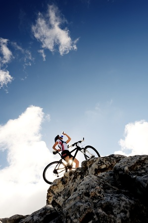 quench: Cyclist drinks water on top of a mountain with bike on a sunny day