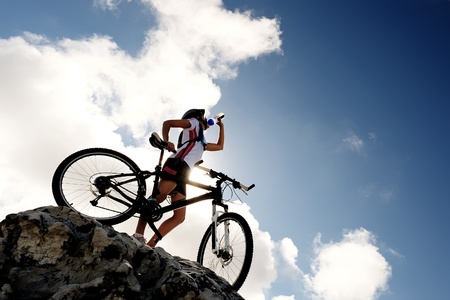 biking: Cyclist drinks water on top of a mountain with bike on a sunny day