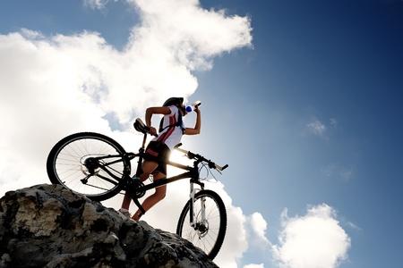 andando en bicicleta: Las bebidas de agua Ciclista en la cima de una montaña con la bici en un día soleado