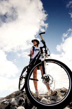 confident mountainbike rider standing and observing the view Stock Photo