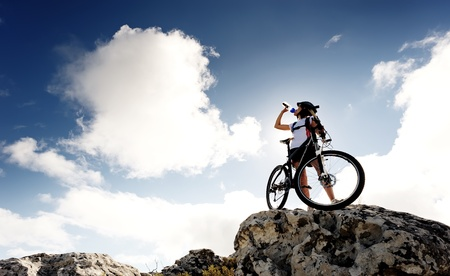 andando en bicicleta: Las bebidas de agua Ciclista en la cima de una monta�a con la bici en un d�a soleado