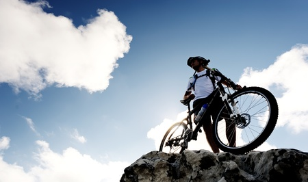 mountainbike: confident mountainbike rider standing and observing the view Stock Photo