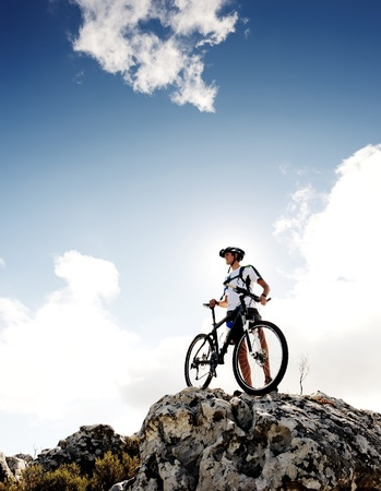 mountain bicycle: confident mountainbike rider standing and observing the view Stock Photo