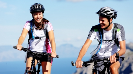 mountain bicycle: Happy carefree mountain bike couple cycling outdoors and leading a healthy lifestyle.  Stock Photo