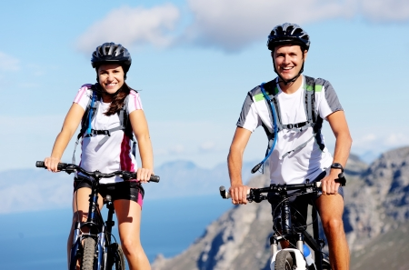 andando en bicicleta: Feliz despreocupados en bicicleta de montaña al aire libre, un par de ciclismo y llevar una vida sana.