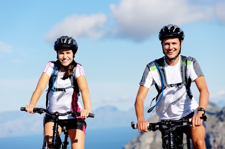 Happy carefree mountain bike couple cycling outdoors and leading a healthy lifestyle. Stock Photo - 12347165