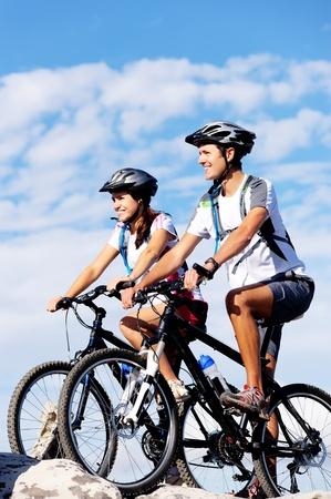 riding bike: Happy spensierati per mountain bike paio all'aperto in bicicletta e che conduce una vita sana.