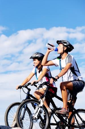 andando en bicicleta: Agua potable Ciclista para asegurar la hidrataci�n y para calmar la sed. Foto de archivo