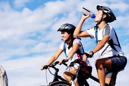 Cyclist drinking water to ensure hydration and to quench thirst.  photo