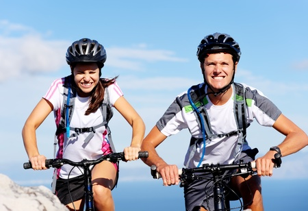 Cycling couple put in exta effor to beat each other to the top of a mountain on their bikes.  photo