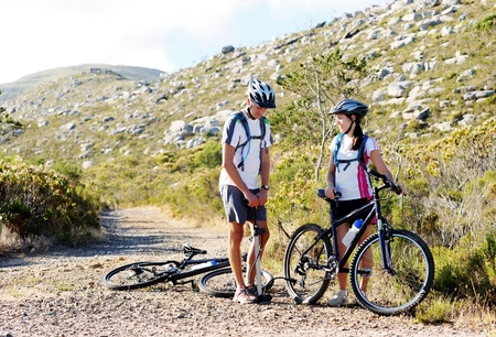 flat tire: Bicycle has flat tyre and man helps his girfriend pump it up. outdoors mountain bike couple. Stock Photo