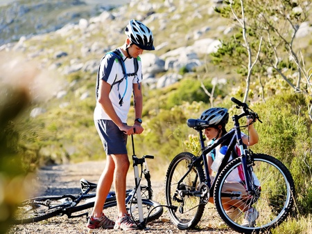 flat tyre: Bicycle has flat tyre and man helps his girfriend pump it up. outdoors mountain bike couple. Stock Photo