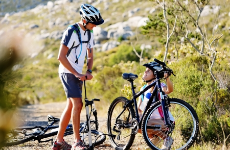 summer tire: Bicycle has flat tyre and man helps his girfriend pump it up. outdoors mountain bike couple. Stock Photo