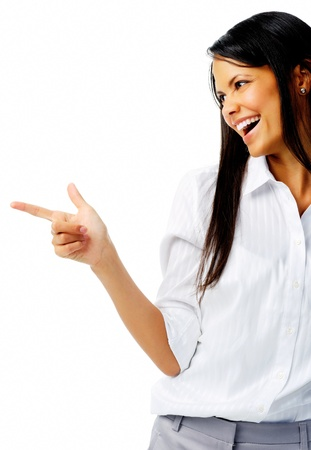 indicate: Laughing businesswoman points to imaginary product in studio, isolated on white