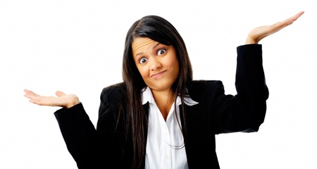 Confused young businesswoman shrugs her shoulders in a clueless gesture Stock Photo