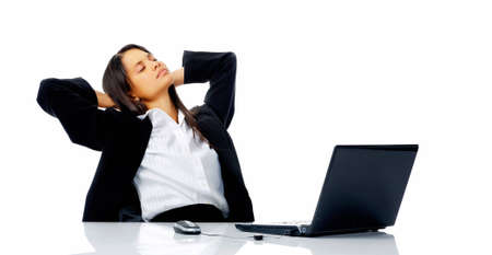 comfotable woman takes a break from her work and leans back in her office chair daydreaming about a vacation. photo