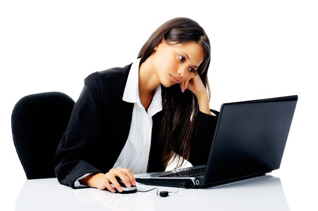 businesswoman working at her desk with laptop computer is stressed, frustrated and overwhelmed by depressiong business situations. isolated on white photo