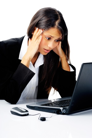 situations: businesswoman working at her desk with laptop computer is stressed, frustrated and overwhelmed by depressiong business situations. isolated on white