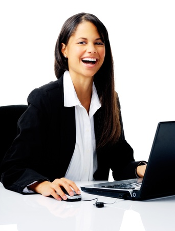 laughing businesswoman uses laptop at her desk, isolated on white photo