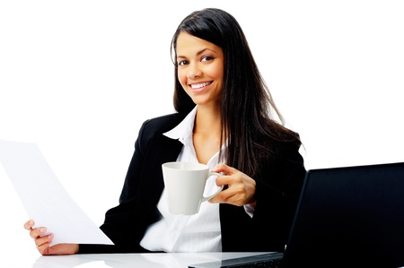 gorgeous businesswoman: attractive businesswoman sitting at her desk, reading stats and graphs on paperwork while enjoying a cup of coffee and smiling isolated on white