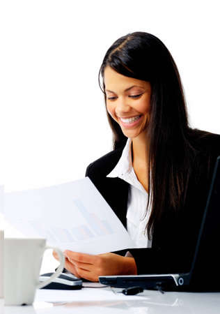 indian professional: attractive businesswoman sitting at her desk, reading stats and graphs on paperwork while enjoying a cup of coffee and smiling isolated on white