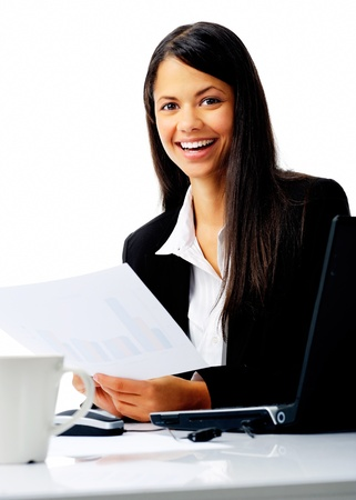 attractive businesswoman sitting at her desk, reading stats and graphs on paperwork while enjoying a cup of coffee and smiling isolated on white photo