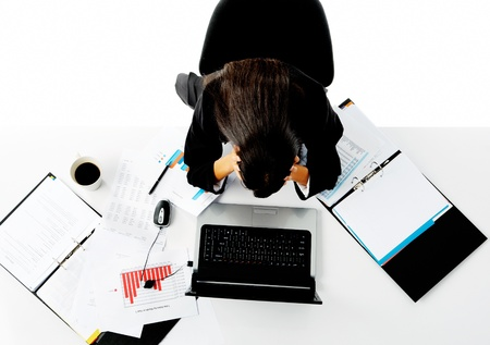 overwhelmed businesswoman holds her head in her hands and is stressed. photo