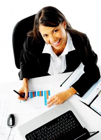 secretaries: mujer que trabaja en su escritorio, dispar� desde arriba. el an�lisis de gr�ficos y estad�sticas de ventas empresaria est� feliz Foto de archivo