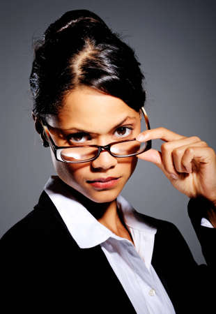 Indian businesswoman tilts and looks over her spectacle frames photo