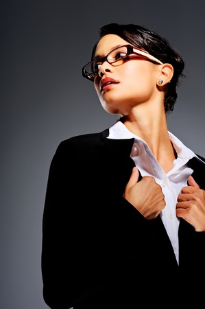 lapels: Mixed race woman in glasses holding the lapels of her business suit