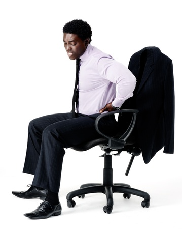 Black businessman in pain from sitting on his office chair with bad posture, long working hours concept. isolated on white photo