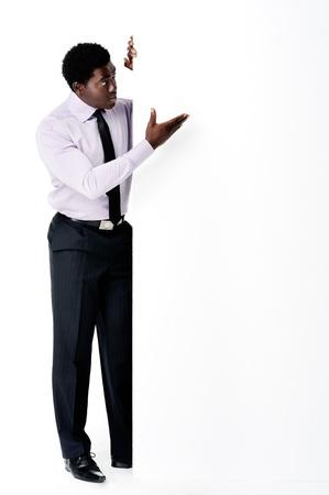leeg bord: Zwarte Afrikaanse zakenman staan met een lege lege raad verstrekken copyspace voor elke vorm van reclame materiaal.