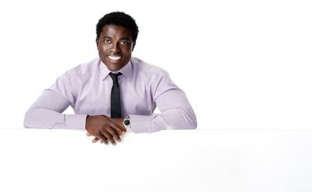 advertising material: Black african businessman standing with a blank empty board providing copyspace for any advertising material.