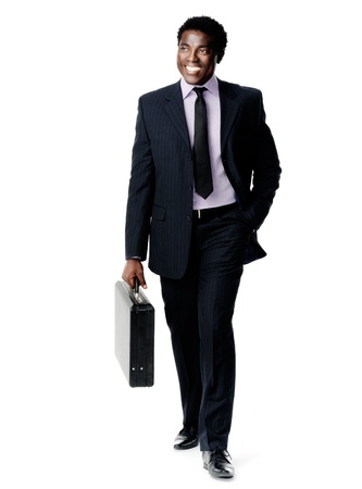 friendly black businessman walking with his briefcase smiling and happy photo