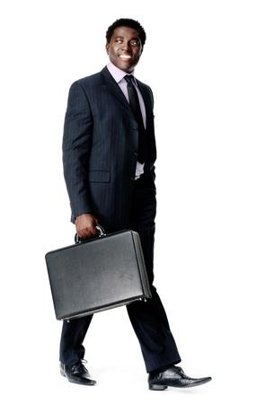 black briefcase: hombre de negocios amigable negro caminando con su malet�n sonriente y feliz Foto de archivo