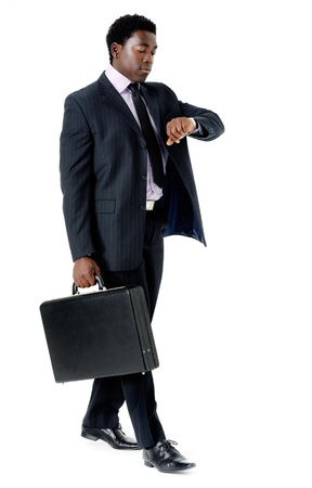 Businessman late for a meeting checking the time and walking with briefcase isolated on white photo