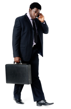 suit case: Black businessman walking and talking on his phone Stock Photo