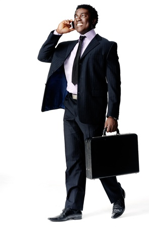 suit case: Happy cheerful young black businessman walking and talking on his cell phone, isolated on white with a briefcase in hand