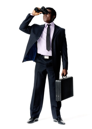 Black African Businessman looking ahead with vision and binoculars while holding a briefcase photo
