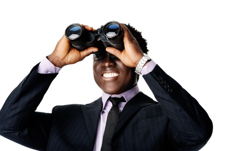 looking forward: confident young black businessman looking through his binoculars at what the future business vision is Stock Photo