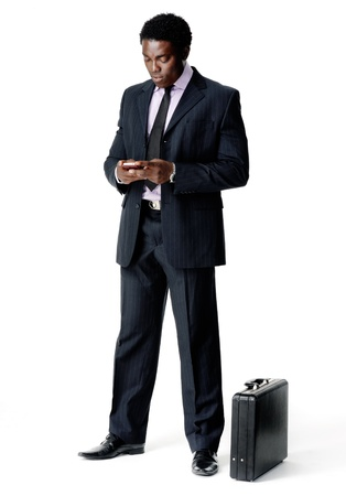 businessman sending a text message with his cell phone while his briefcase rests on the floor  isolated on white photo