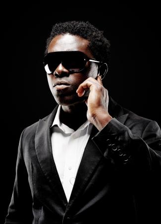 sicario: Guardaespaldas negro africano o el agente secreto en un fondo oscuro con iluminaci�n espectacular gesto hacia la c�mara que llevaba un traje