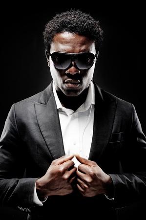 sicario: Guardaespaldas de negro africano o el agente secreto en un fondo oscuro con el gesto de iluminaci�n espectacular hacia la c�mara que llevaba un traje Foto de archivo