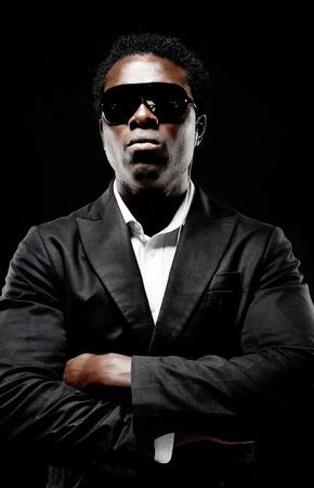Black African Leibwächter oder Geheimagenten auf einem dunklen Hintergrund mit dramatischen Beleuchtung Geste in Richtung Kamera im Anzug Standard-Bild