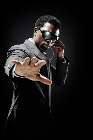Black african bodyguard or secret agent on a dark background with dramatic lighting gesture towards camera wearing a suit photo