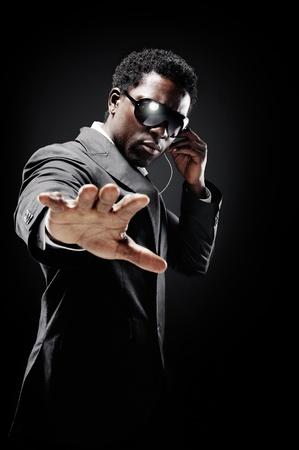 sicurezza sul lavoro: Guardia del corpo nero africano o agente segreto su uno sfondo scuro con gesto illuminazione drammatica verso la telecamera che indossa un abito Archivio Fotografico