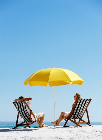 Beach summer couple on island vacation holiday relax in the sun on their deck chairs under a yellow umbrella. Idyllic travel background. Foto de archivo